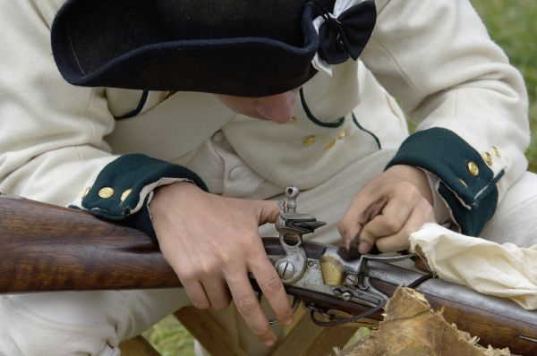 French soldier cleaning his musket at a reenactment on the Yorktown Battlefield, Virginia. Digital photograph of a National Park Service event at Yorktown Battlefield on the 225th anniversary of the surrender