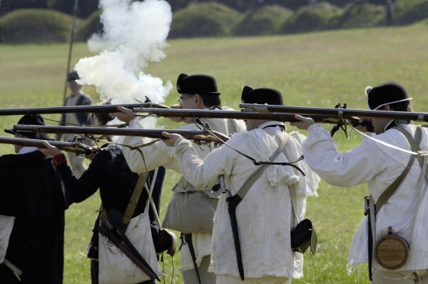 Continental Army reenactors firing their muskets at Yorktown battlefield, Virginia. Digital photograph of an 18th century living history demonstration at Colonial National Park Virginia