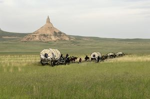 Oregon Trail pioneers passing Chimney Rock